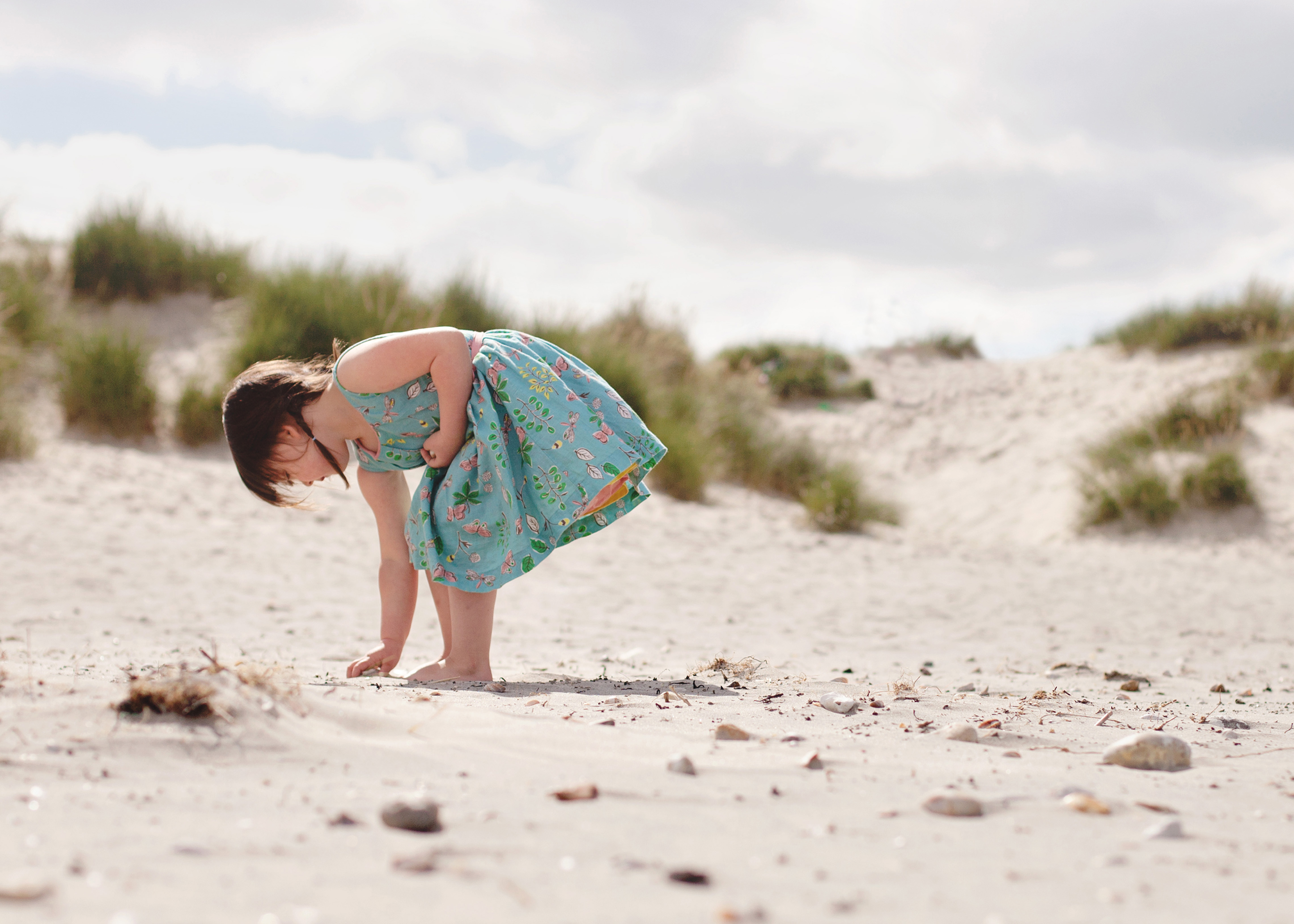 Photograph of girl finding shells on West Wittering beach by Moira Lizzie Photography