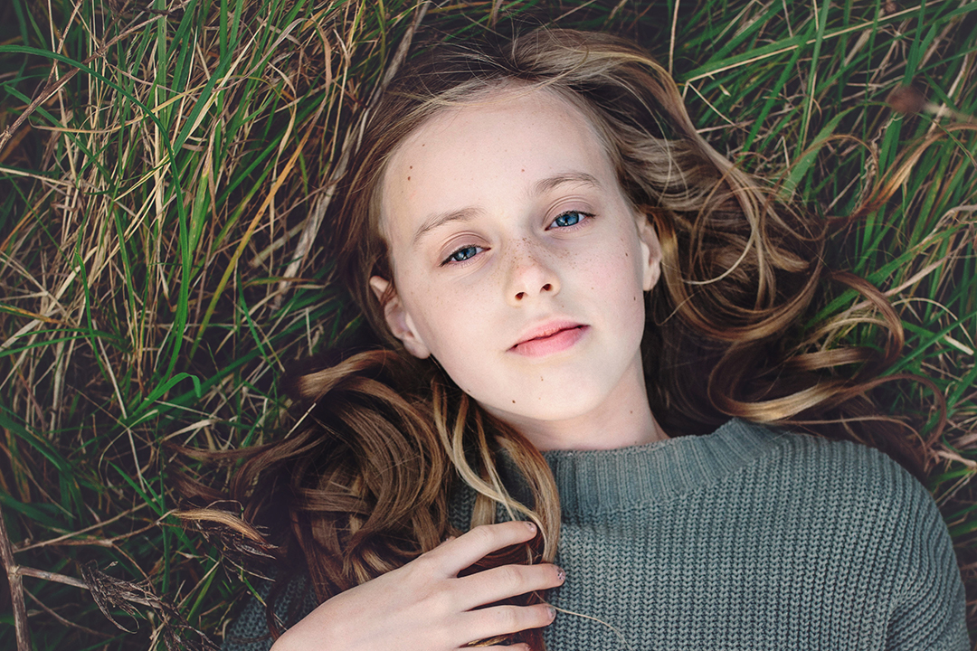 Portrait of girl laying in grass at Portchester Castle by Moira Lizzie Photography