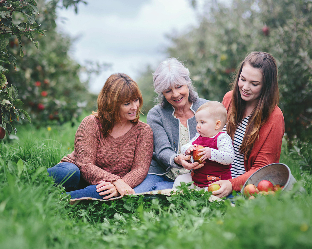 Autumnal image of four generations of women seated in apple orchard