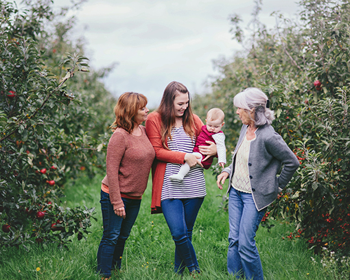 Autumnal image of four generations of women set in apple orchard