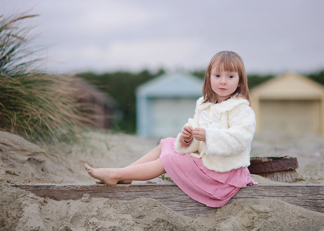 Girl on sandy beach infront of beach huts at West Wittering by Moira Lizzie Photography