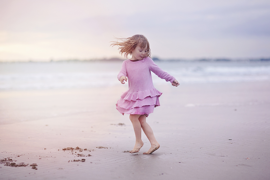 Gril spinning on sandy beach at sunset by Moira Lizzie Photography