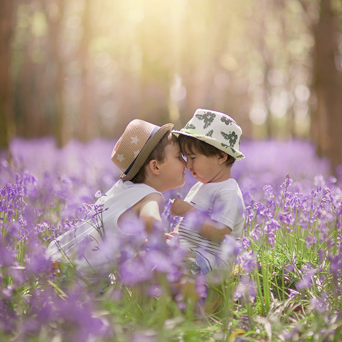 Boys playing in bluebell wood during Spring by Moira Lizzie Photography