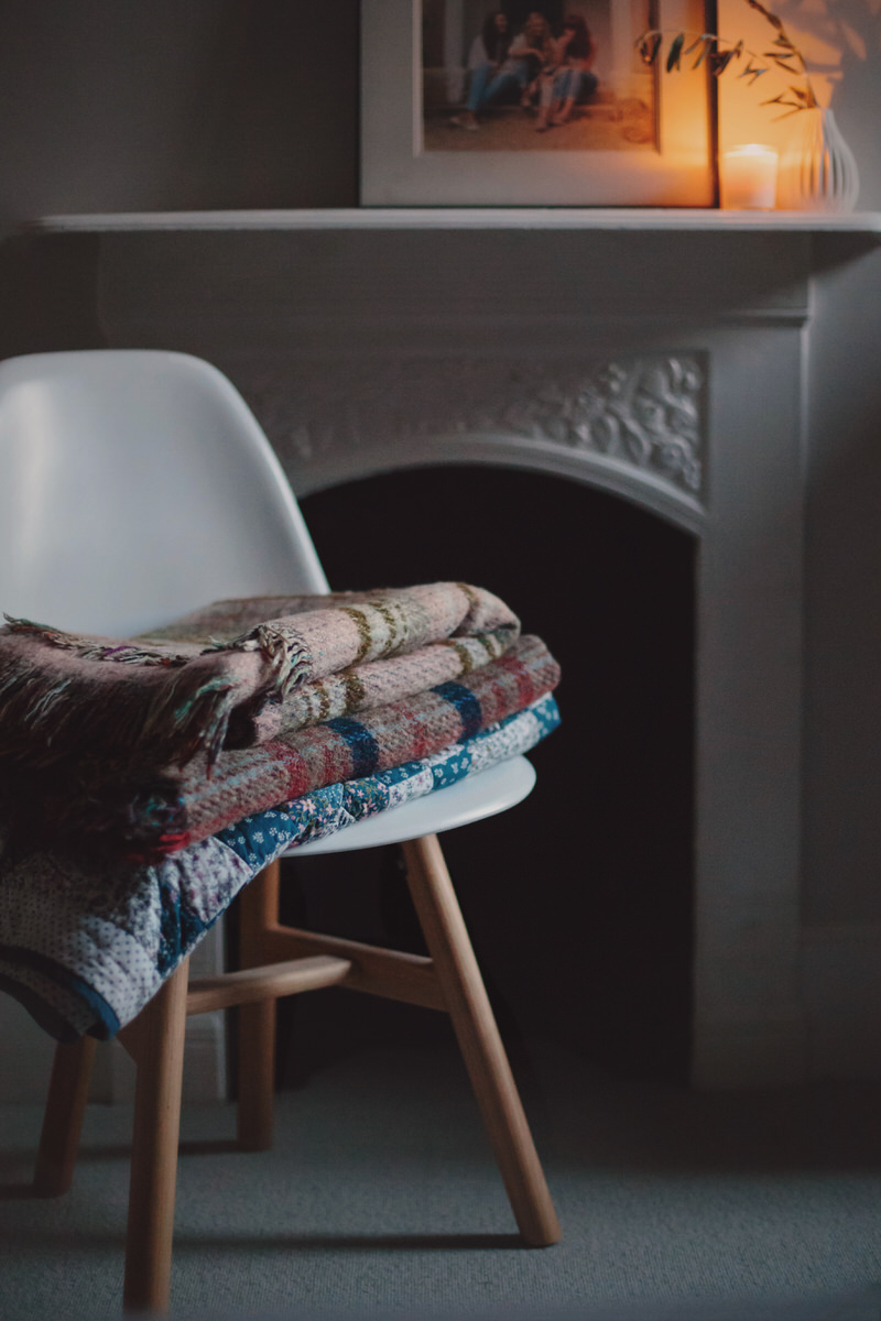 Chair stacked with folded blankets and quilt perfect for styling a hygge photoshoot