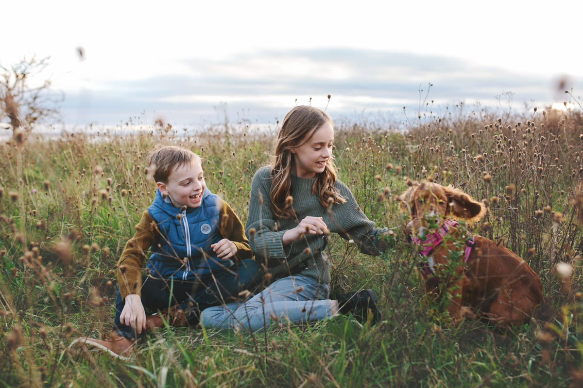 Hygge image of fun family moment being shared between siblings and their dog