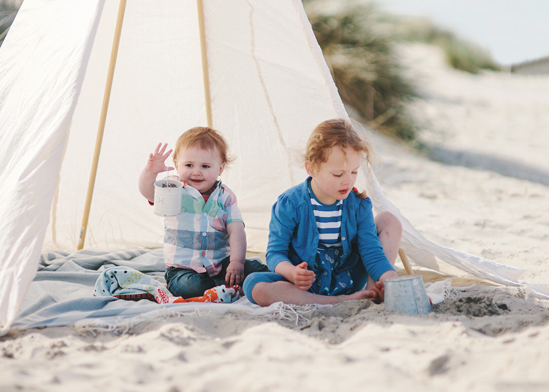 Siblings playing in sand on beach by Moira Lizzie Photography