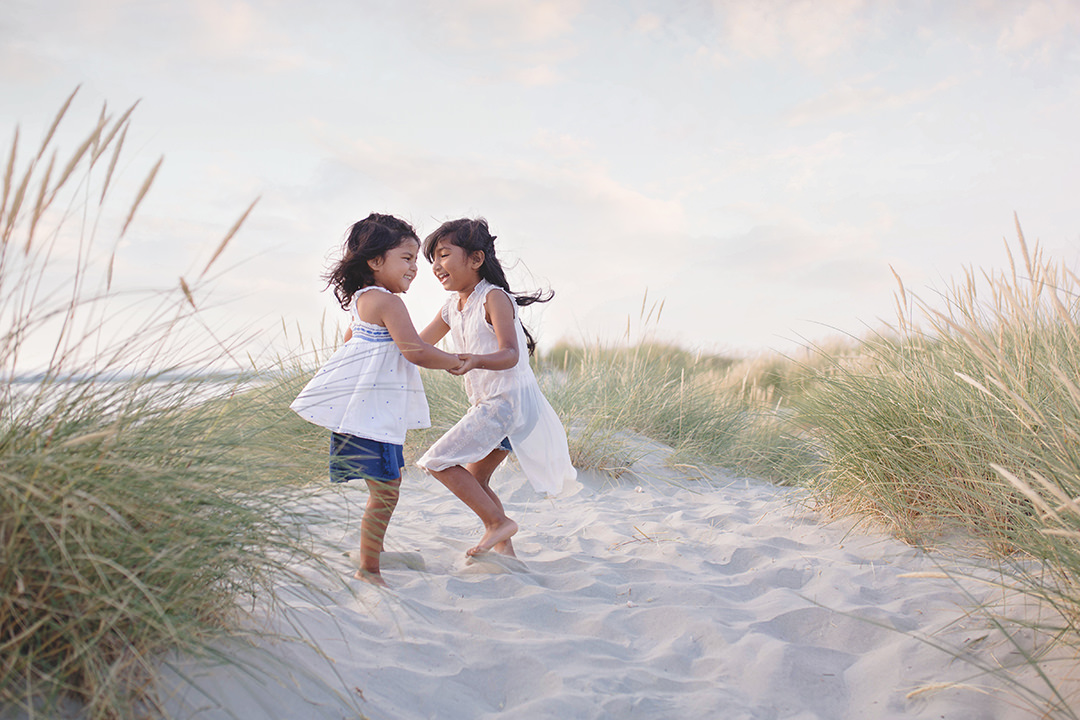 Siblings dancing in sand dunes by Moira Lizzie Photography