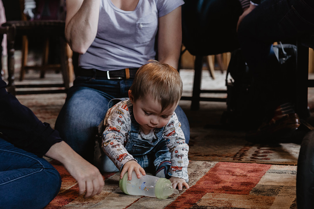 Documentary photograph of baby boy playing on floor