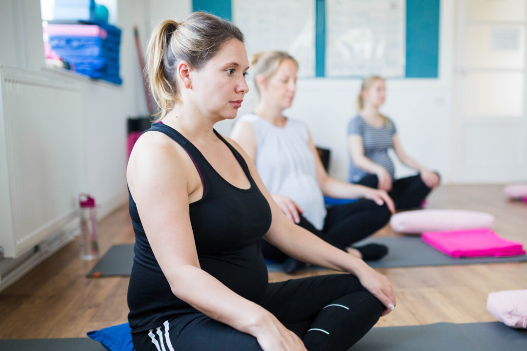 Image of pregnancy yoga class attendee breathing exercises