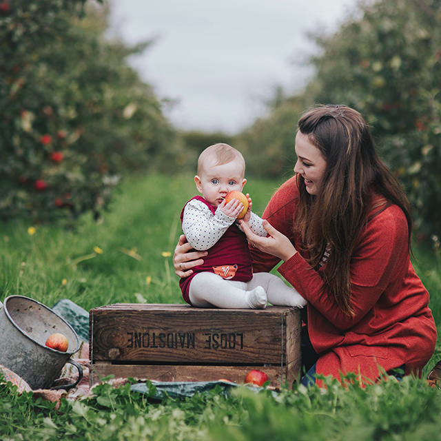 Image of mother with baby in apple orchard by Moira Lizzie Photography